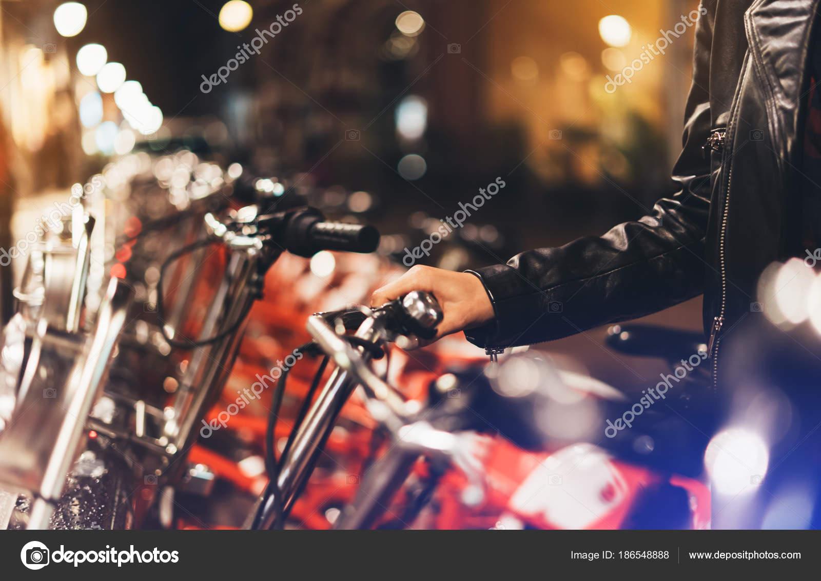 Giovane ragazza giacca pelle nera utilizzando bici bokeh sfondo