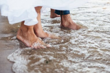 couple in love standing barefoot on the beach wet sand