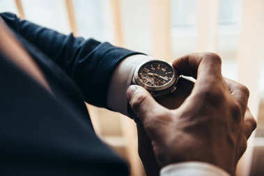 stylish mechanical watch on the hand of a man who watches time