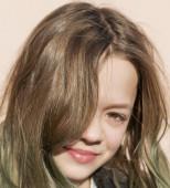Egy fiatal lány sötét kabátban pózol a kamera előtt.