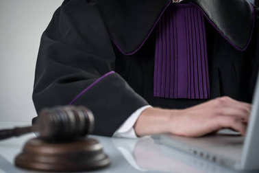 Justice and law concept. Male judge in a courtroom with the gavel and working with book