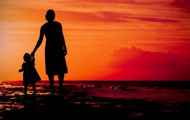 Silhouette of mother and daughter walking on beach at sunset