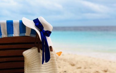 hat and bag with suncream on tropical beach
