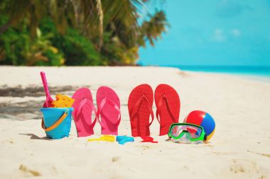 Colored slippers, toys and diving mask at beach