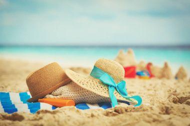 hats, bag, suncream and glasses on beach