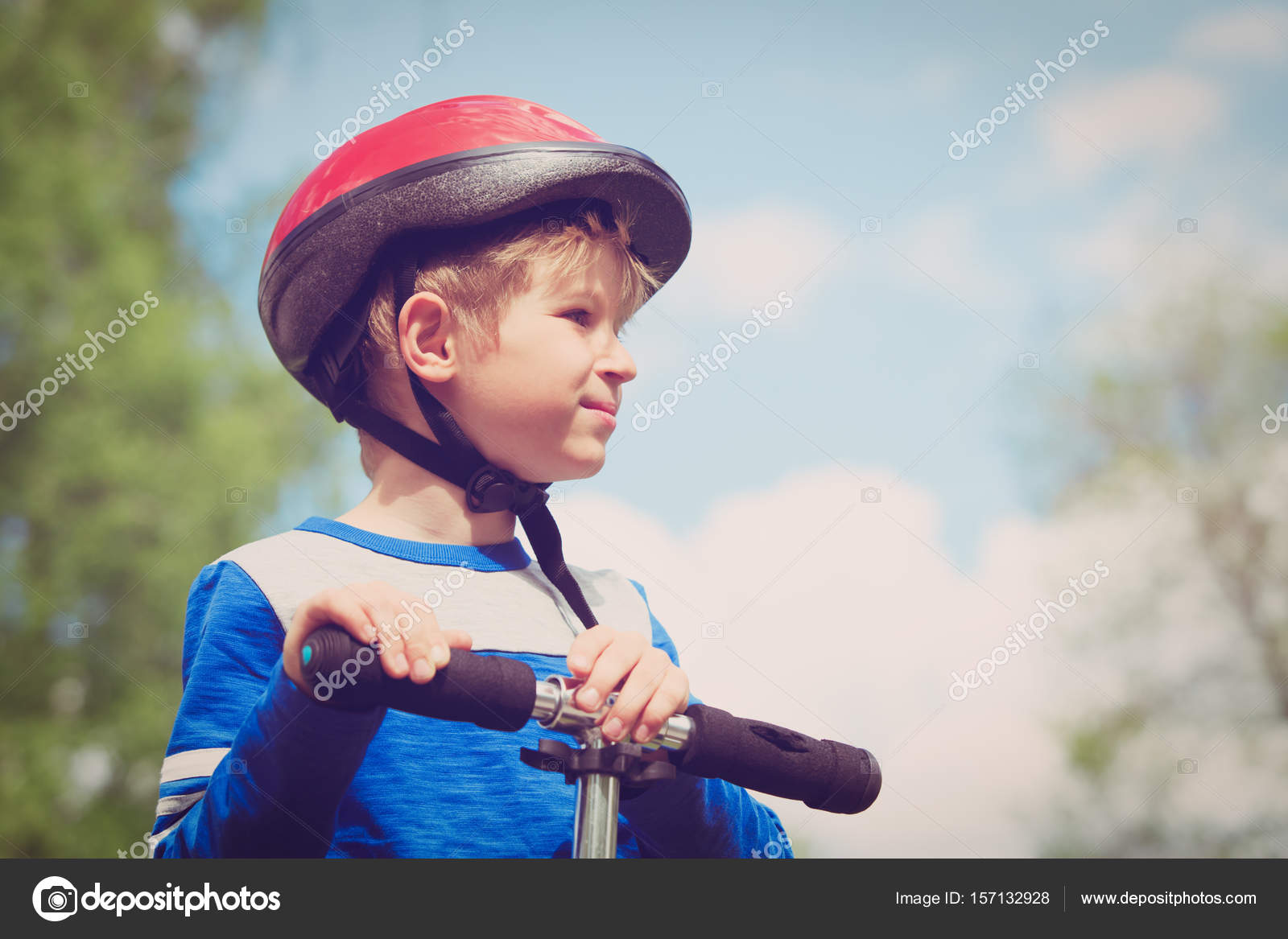 f05d385a2c28f Cute little boy with helmet riding scooter in nature — Photo by ...