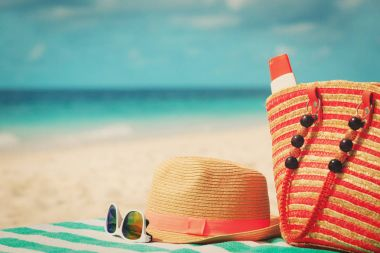hat, sunglasses and bag with suncream on beach
