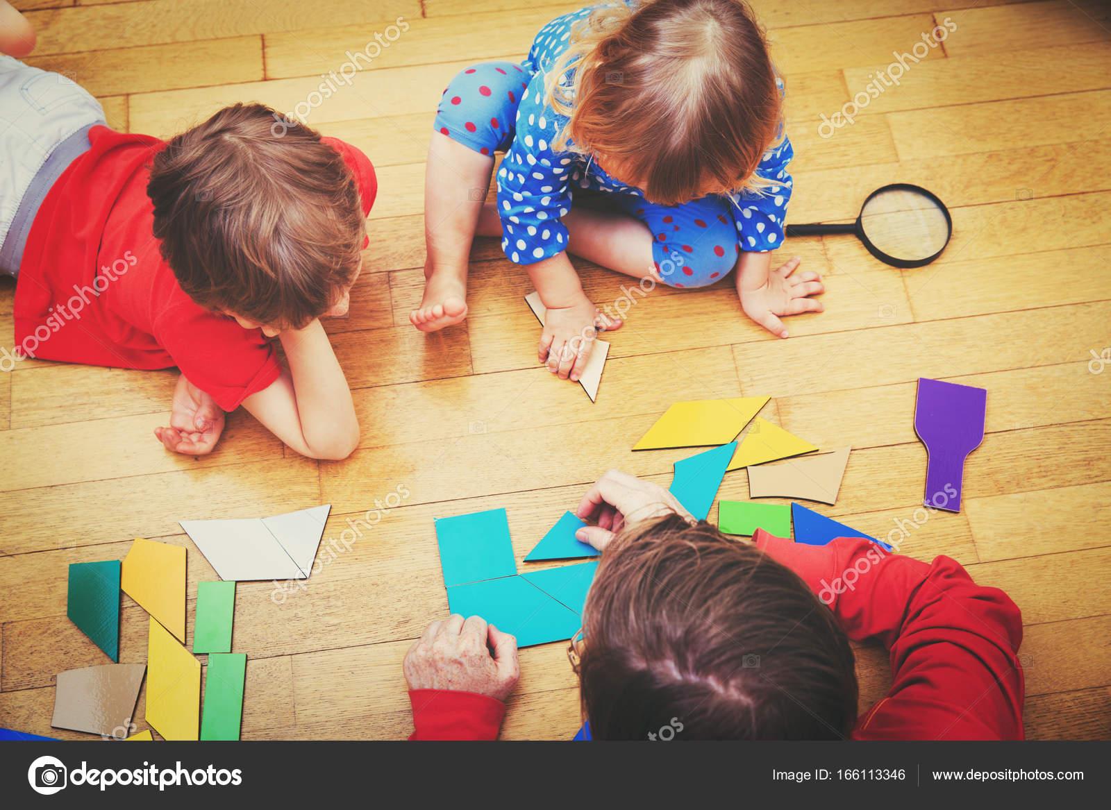 Lehrer und Kinder spielen mit geometrischen Formen — Stockfoto ...