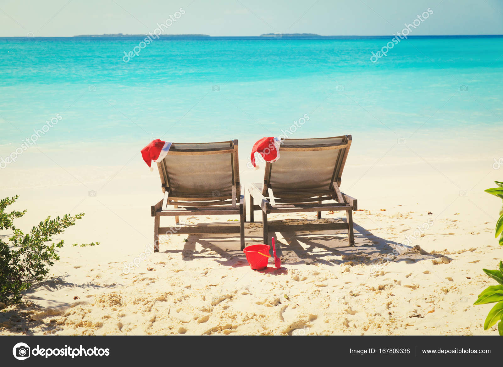 christmas on beach chair lounges with santa hats at sea. Black Bedroom Furniture Sets. Home Design Ideas