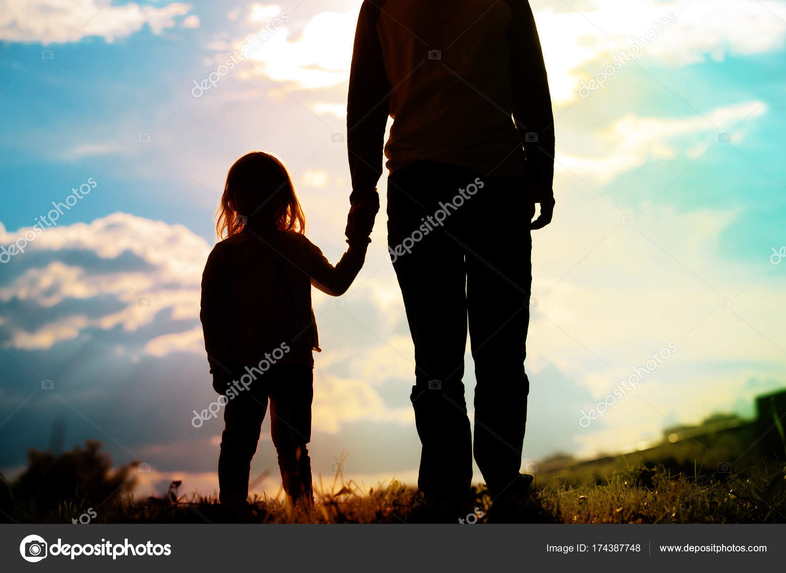 Silhouette Of Father And Daughter Holding Hands At Sunset Stock