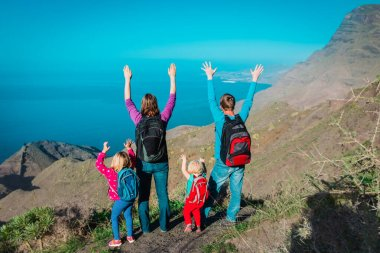 mom, dad with kids travel in mountains near sea, family in Canary islands, Spain