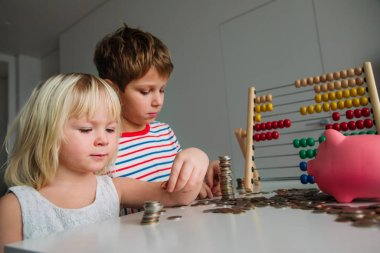 kids count and save money, girl and boy put coins into piggy bank