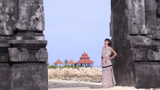 junge sexy Dame in einem Kleid bleibt in der Nähe der balinesischen Tore und bewundert die Aussicht. Asiatisches Sommerhaus und Meer im Hintergrund. 1080p, 50 fps, full hd.