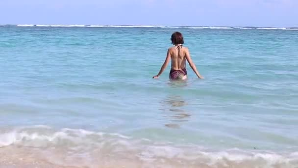 Young and hot sexy woman come into the ocean. Beautiful slim body, summer holidays vacation travel. Rear View, sandy beach, tropical view. Bali, Indonesia. Carefree and happy lady. Beach scene.