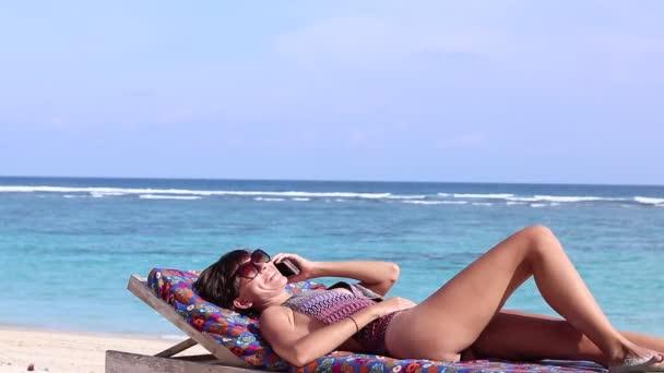 Szexi vonzó fiatal kaukázusi nő a gyönyörű trópusi strandon használ okostelefon és mosolygott. Relaxált hölgy napfürdők a nyugágyon. Fit női élő egészséges wellness életmód a strandon.