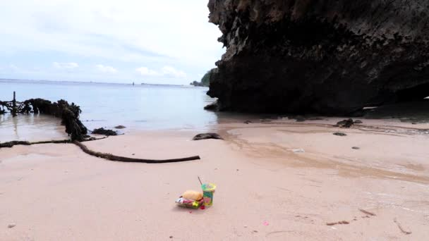 Obětiny bohům v Bali s květinami, jídlo, vonných tyčinek a čaj pít na krásné pláži. Bali, Indonésie
