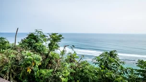Panorama Time lapse, tropical scene, view to the ocean from the cliff in a  sunny day  Awesome sky, blue water, green palms  Tropical island Bali,  Indonesia