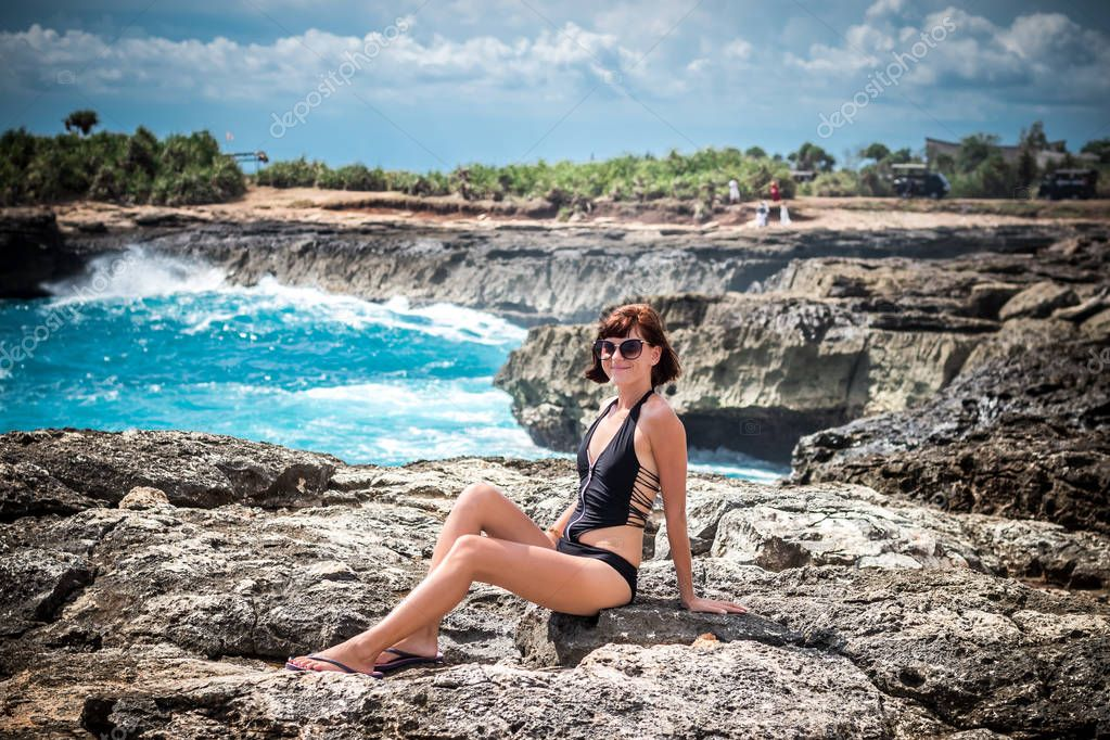 Portrait of young and sexy woman on the rocks near the wild ocean. Storm, huge waves coming and splashing. Tropical island Nusa Lembongan, Indonesia, Asia. The name of the place is Devils Tear.