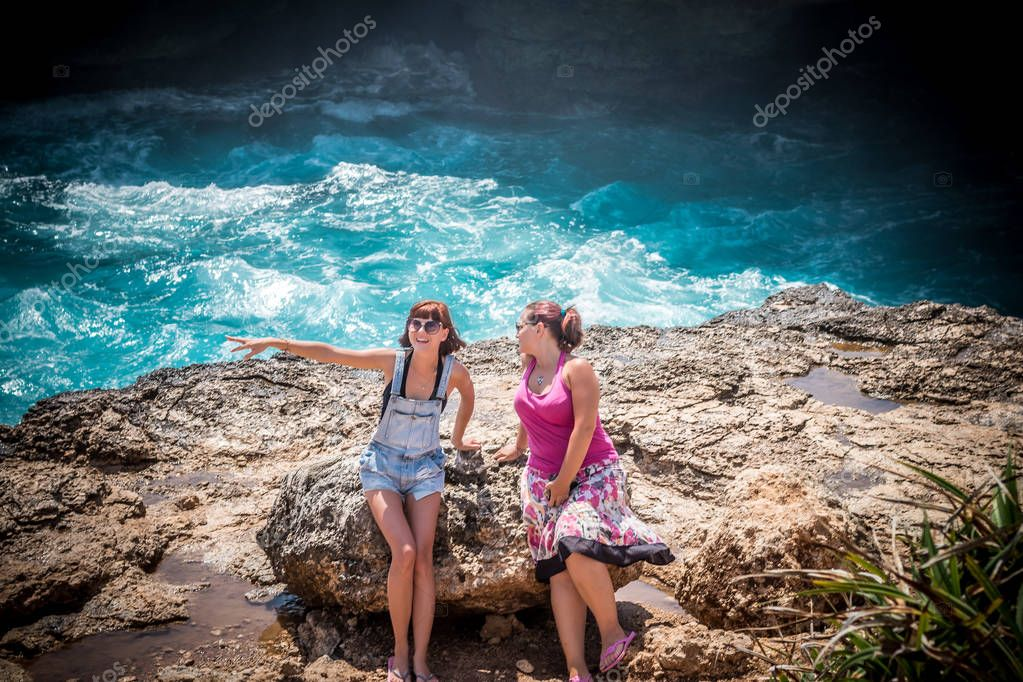 Two young and sexy women on the rocks near the wild ocean. Storm, huge waves coming and splashing. Tropical island Nusa Lembongan, Indonesia, Asia. The name of the place is Devils Tear.