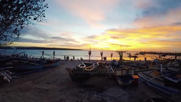 Krásný západ slunce na pláži Jimbaran, tropický ostrov Bali, úžasné barvy, světlo světlo prosvítající závojem mračen nad Indickým oceánem. Západ slunce nad pláží Bali oceánu. Rybářské lodě, rybářské vesnice
