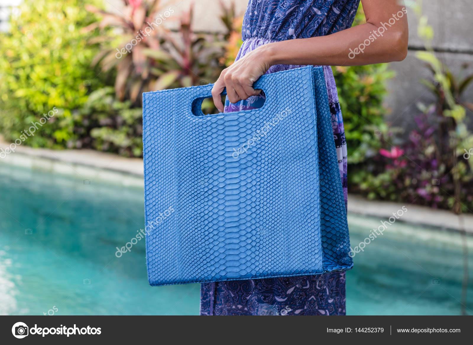 f6d869cc83 Μοντέρνα όμορφα μεγάλα μπλε δέρματος φιδιού python τσάντα στο μπράτσο του  κοριτσιού σε ένα μοντέρνο φόρεμα