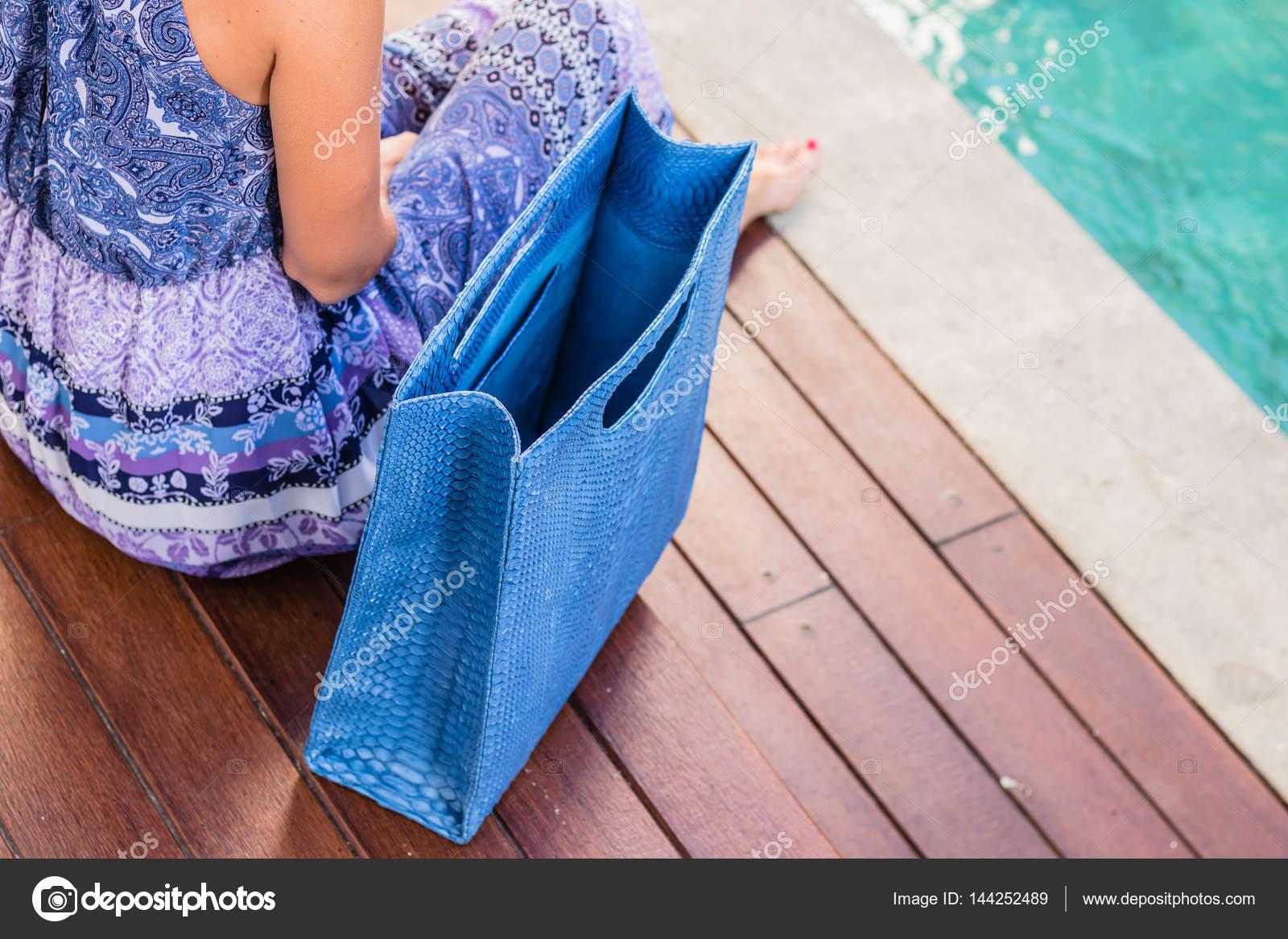 1a98de91c0 Μοντέρνα όμορφα μεγάλα μπλε δέρματος φιδιού python τσάντα κοντά το κορίτσι  σε ένα μοντέρνο φόρεμα
