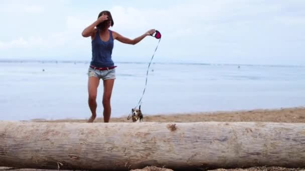 Frau und niedlicher Beagle-Hund spielen am Strand der tropischen Insel bali, sanur, Indonesien.