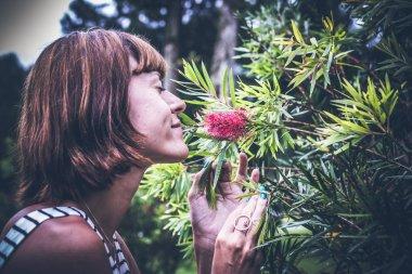 Portrait of beautiful woman posing among blooming asian flowers on Bali island, Indonesia.