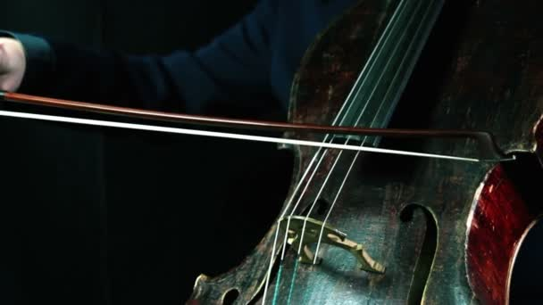 Alten Cellospiel auf einem schwarzen Hintergrund closeup