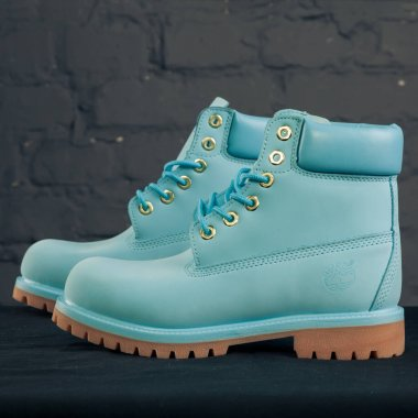 New beautiful colorful and nice Timberland tracking shoes, sneakers, trainers shows logo with a brand box on abstract background. Sport and casual footwear concept. Kyiv, Ukraine-November 24, 2017