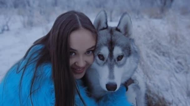 Krásná dívka objímá husky pes