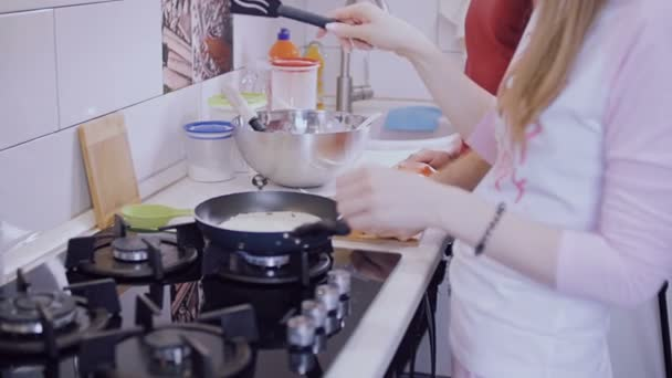 Mladý pár připravují své vlastní snídani v kuchyni.