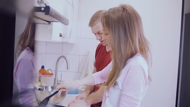 Mladý pár je vaření palačinky s rybami v kuchyni.