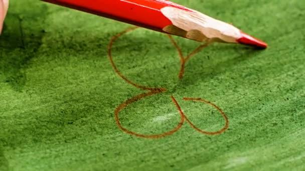 Makró fotózás. Egy piros virág ceruza rajz papír borított zöld festék.