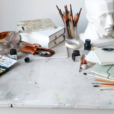 Interior of painting studio of freelance artist. Gypsum head, brushes, pencills, ink and paint bottles with sketchbooks on the table. Freelance artist lifestyle concept. Square composition. Copy space