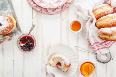 Tea time with festive sufganiyot donuts filled with jelly and covered with sugar powder. White wooden background, bright lighting. Horizontal composition.