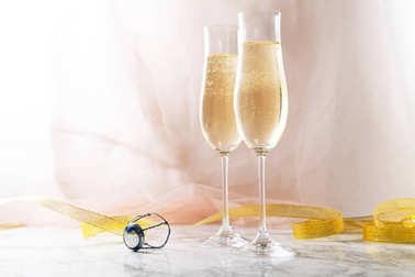 Two flute glasses with champagne on marble background. Pink transparent fabric. Soft light. Horizontal composition