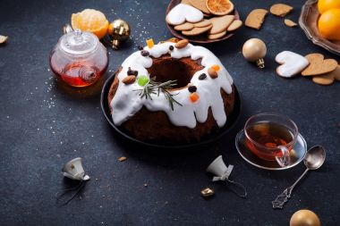 Traditional christmas cake with dried fruits soaked in rum and sugar glaze. Teatime with heart-shaped ginger cookies. Christmas background with festive decoration. Horizontal composition
