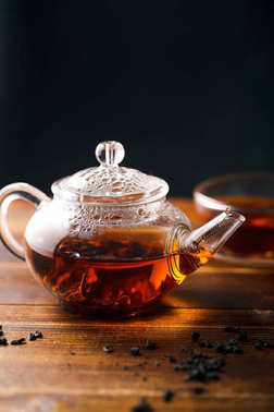 transparent glass tea pot with hot black tea on wooden table