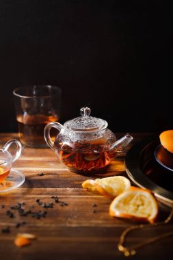 small glass teapot with hot black tea and glass with squeezed orange slices on wooden background