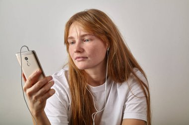 young red-headed woman with freckles holding phone while answering video call with plugged in earphones