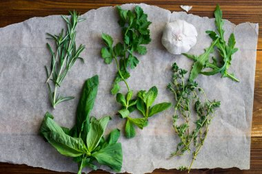 collection of fresh culinary herbs in small bunches with garlic clove on wooden background