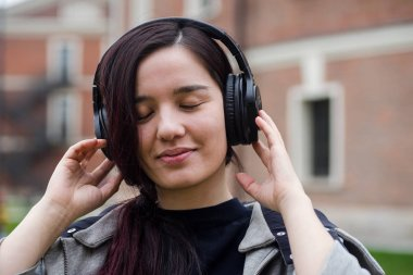 portrait of young asian girl with headphones listening to the music and dancing at the street