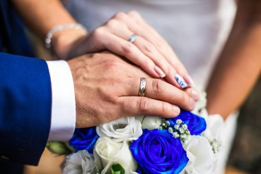 Newly wed couple's hands with wedding ring, white and blue roses