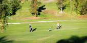 Tři golfisté na zeleném golfovém hřišti v Kalifornii