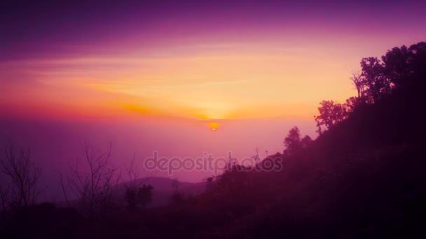 Východ slunce z vrcholu hory s mlhou a siluety stromů