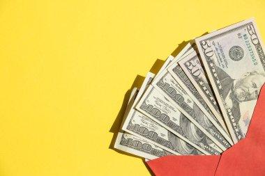 Bir yığın Amerikan doları, açık kırmızı bir zarfın içinde banknotlar, sarıya karşı izole edilmiş. Çevrimiçi alışveriş. Zenginlik ve refah. Zarfta nakit para var. İkramiye, ödül, ikramiye. Anlaşıldı.