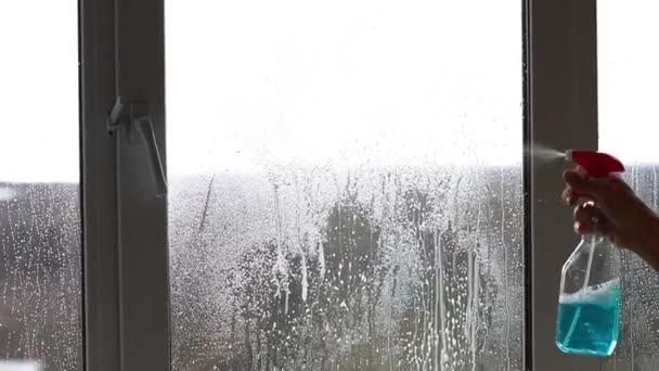 lidé, domácí práce a úklid koncept, muž čištění okna s hadrem a čistící sprej doma. Spraying láhev střílí vodu v pulvelizer láhev zblízka, úklid konceptu.mytí oken