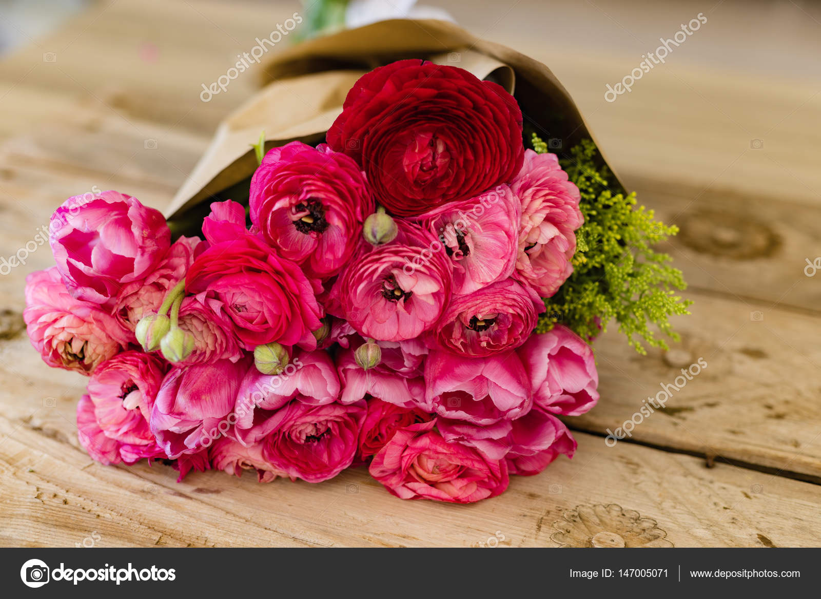 Bouquet Of Pink Ranunculus Wrapped In Craft Paper Lying On Rusti