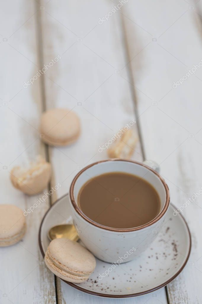 a cup of coffee with pink macaroons